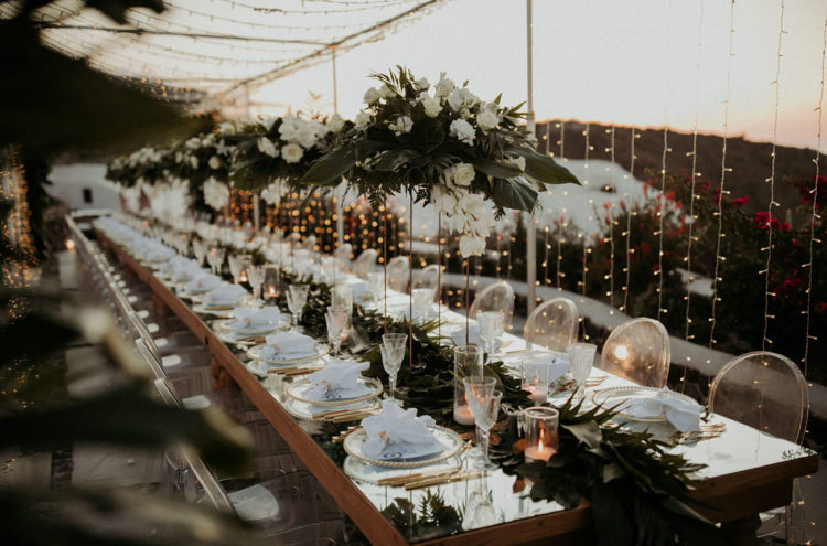 The table was set with white blooms and greenery, centerpieces and a runner, and with touches of gold for more chic