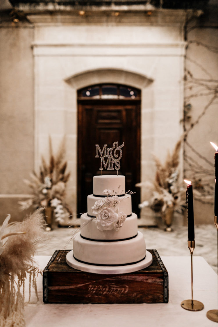 The wedding cake was white, with black ribbons and white sugar blooms