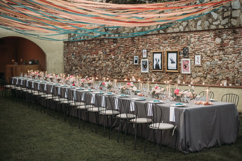 The wedding reception took place in the same house, there were pastel adn bright blooms and matching ribbons hanging over the table