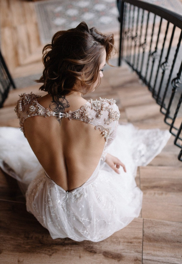 a beautiful lace wedding dress with an open back and gorgeously embellished shoulders plus a couple of buttons