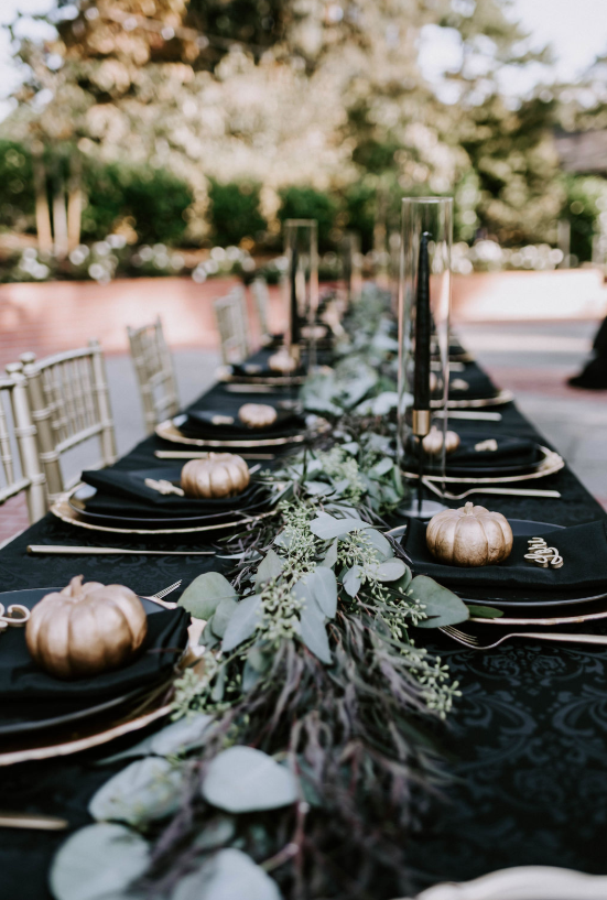 the reception tables were done in black and gold, with black candles and gold pumpkins