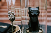 09 Some whimsy details skeleton hand glasses and black cat candles added to the ambience