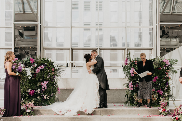 The ceremony space was done with two half walls fully covered with greenery and pink and white blooms