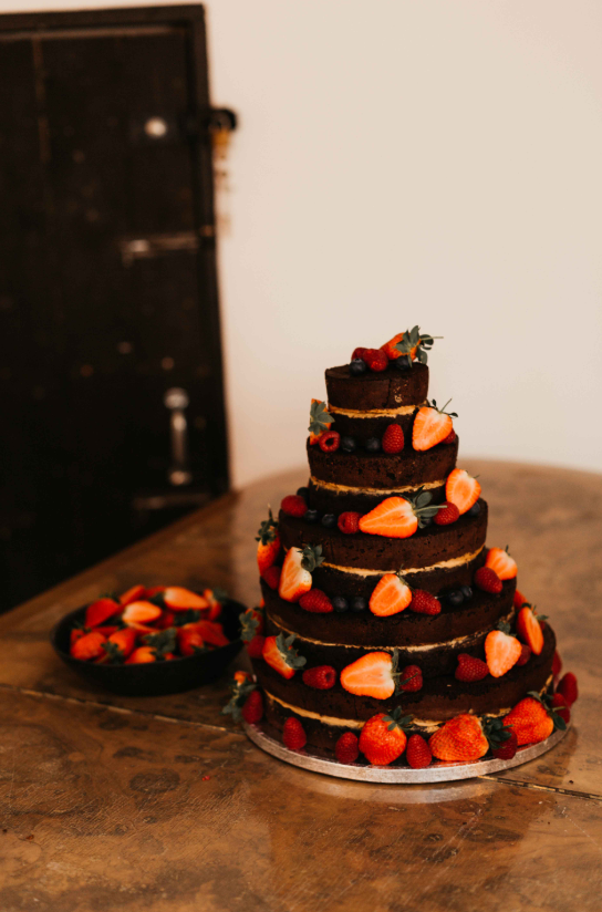 The naked chocolate wedding cake was done with fresh berries and looked super yummy