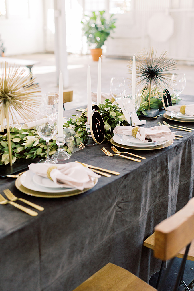 The wedding tablescape was done with a graphite grey tablecloth, a greenery runner, some gold touches and embroidered constellations