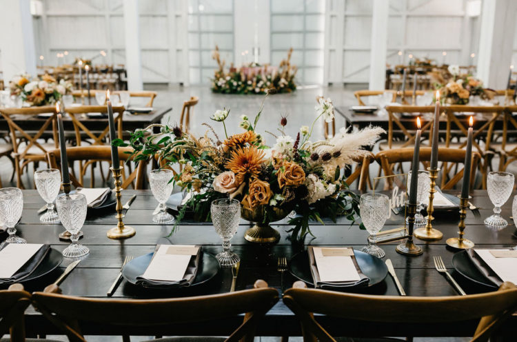 The wedding tablescape was done with an uncovered table, black candles, peachy and rust blooms and gold touches