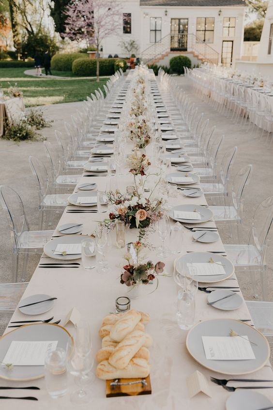 a neutral wedding table with neutral and pastel blooms, greenery and lilac plates with gold rims