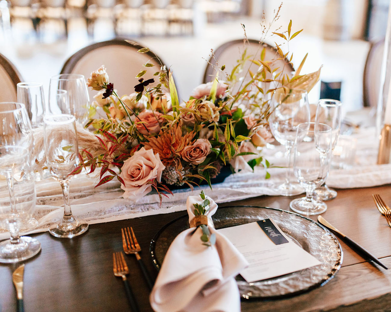 The wedding reception was done with lush and textural arrangements, a lace runner, glass chargers