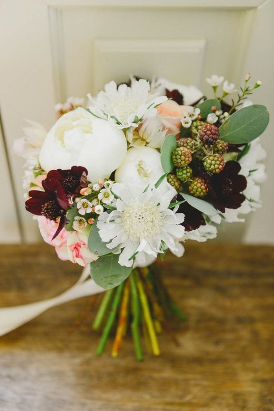 a chic and cool summer wedding bouquet with white and burgundy blooms and berries
