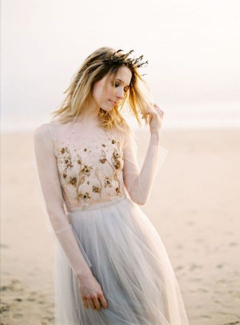 a light blue wedding gown with sheer parts and an embroidered and embellished bodice for a beach bride
