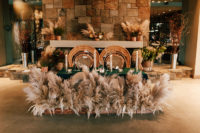 11 The sweetheart table was done with pampas grass, candles and bold blooms