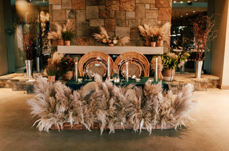 The sweetheart table was done with pampas grass, candles and bold blooms