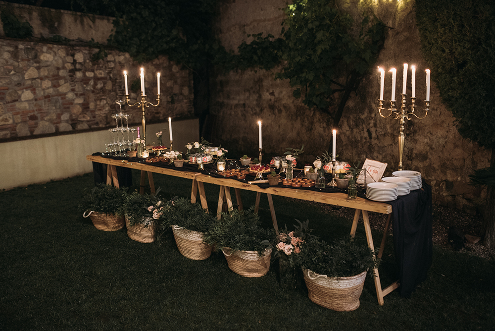 The sweets table was styled in a very elegant way, with candles, sweets and baskets with greenery