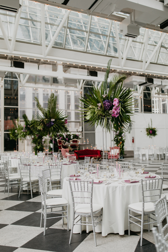 The tables were decorated  with pink linens, pink candles and tall tropical centerpieces of purple and pink