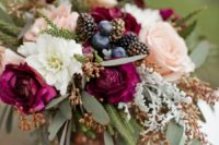 11 a colorful fall wedding centerpiece with pastel and bright blooms and some gilded blackberries and blueberries