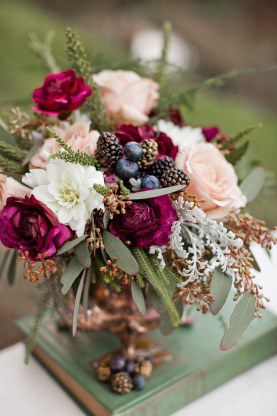 a colorful fall wedding centerpiece with pastel and bright blooms and some gilded blackberries and blueberries
