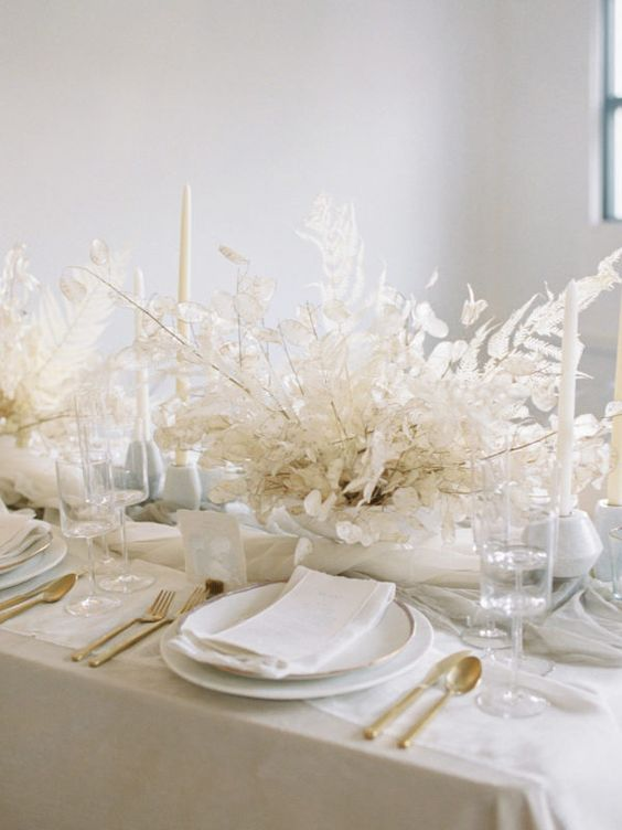 a neutral, almost white wedding tablescape with dried blooms, gold cutlery and white candles