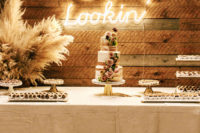 12 A stylish wedding dessert table with pampas grass, lots of sweets and a naked wedding cake with blush blooms