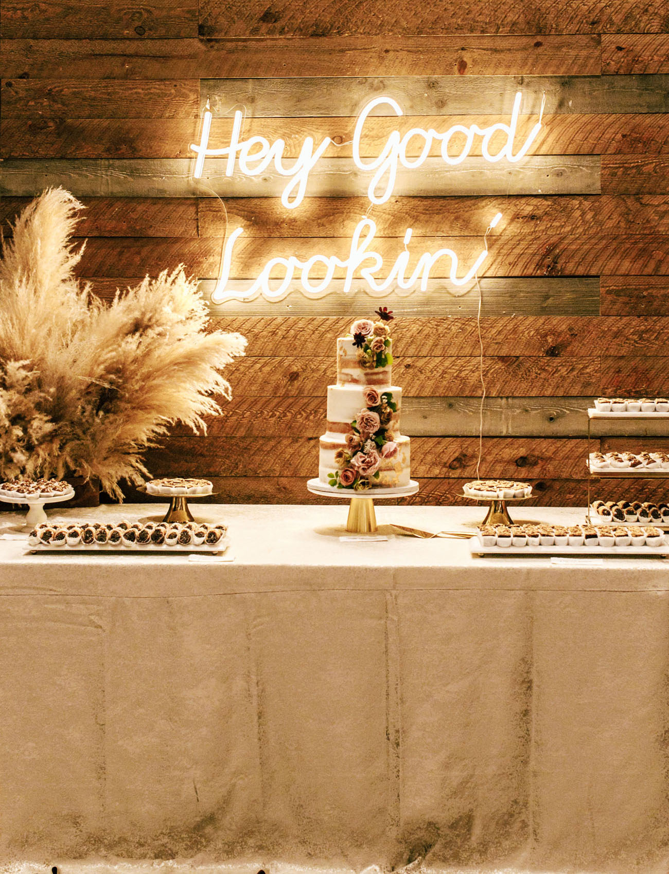 A stylish wedding dessert table with pampas grass, lots of sweets and a naked wedding cake with blush blooms