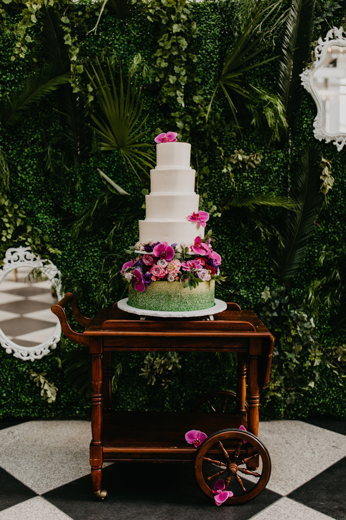 The wedding cake was white decorated with pink blooms and on a pillow of lush bright flowers