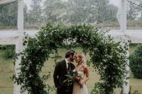 12 a very lush and textural circle greenery wedding arch with lots of different leaves and vines