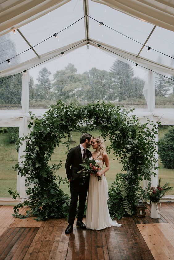 a very lush and textural circle greenery wedding arch with lots of different leaves and vines