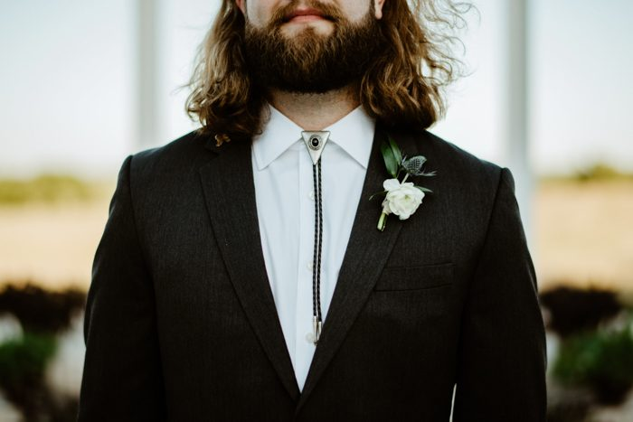 a bolo tie for the groom is a great idea to add a slight Western feel to the wedding without going too far