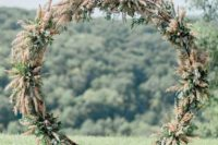 13 a cool circle wedding arch covered with pampas grass and greenery to achieve a cool wild look