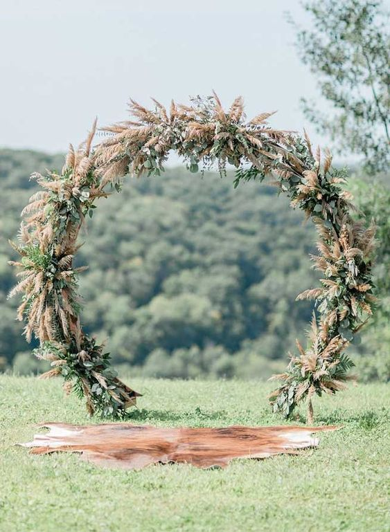 a cool circle wedding arch covered with pampas grass and greenery to achieve a cool wild look