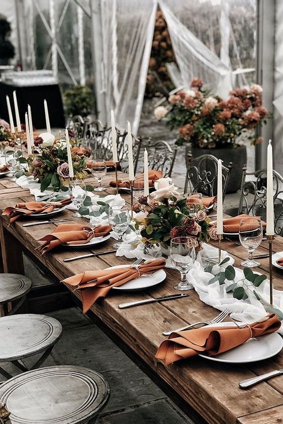 spruce up the tablescape with chic rust blooms and rust-colored napkins to give it an edge