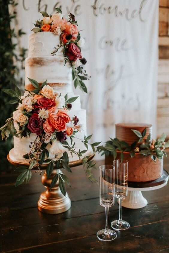 a rust wedding cake with blooms and greenery and a naked wedding cake decorated with rust-colored blooms