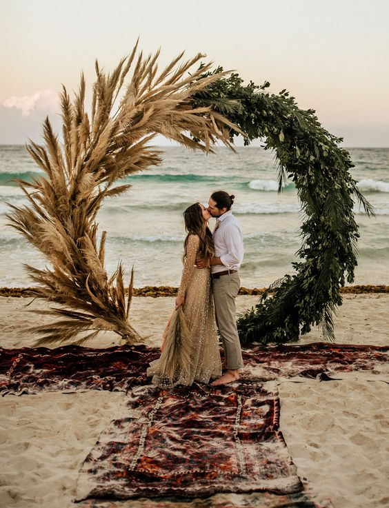 a stunning circle wedding arch decorated with tropical greenery and pampas grass