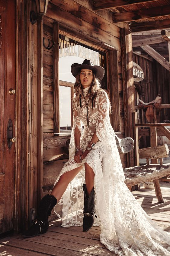 a cowboy hat and cowboy boots plus a bolo tie over a heavenly beautiful lace wedding dress