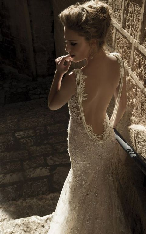 a lace sheath wedding dress with a pearl back necklace that makes a fashion statement