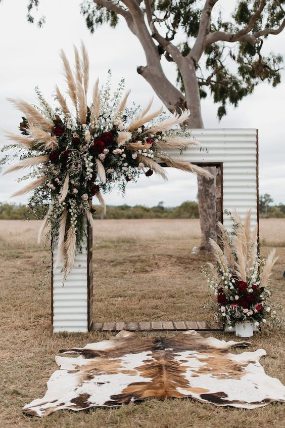 a Western-inspired wedding arch done with pampas grass, blush and burgundy blooms and a cowhide rug