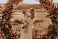 16 a bold and lush wedding arch decorated with blooms, greenery and pampas grass on top
