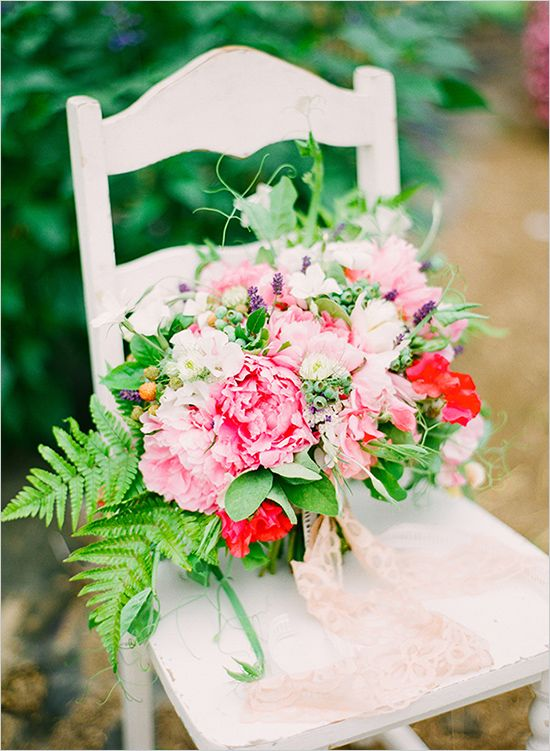 a chic summer wedding bouquet with red and pink blooms, greenery and lavender for much texture