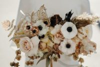 18 a chic wedding bouquet of white anemones, blush and dried roses, dried leaves, seed pods and dark foliage
