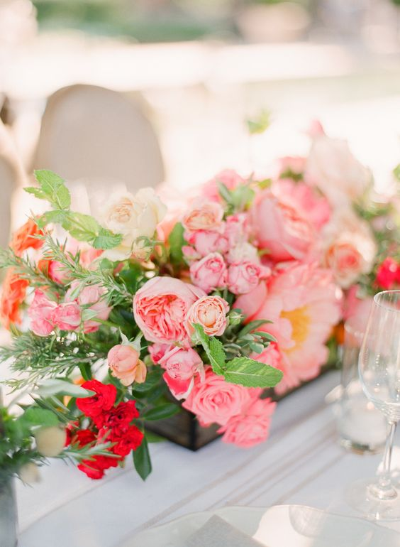 a wooden box with sherbet pink blooms and much textural greenery for a wedding centerpiece