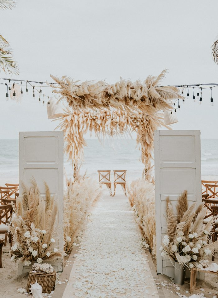 a fantastic all-white wedding ceremony space with pampas grass, white blooms, white doors and wicker lamps