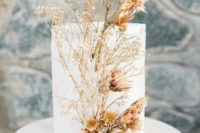 20 a minimalist white wedding cake decorated with dried blooms looks ethereal and very unusual, idela for the fall