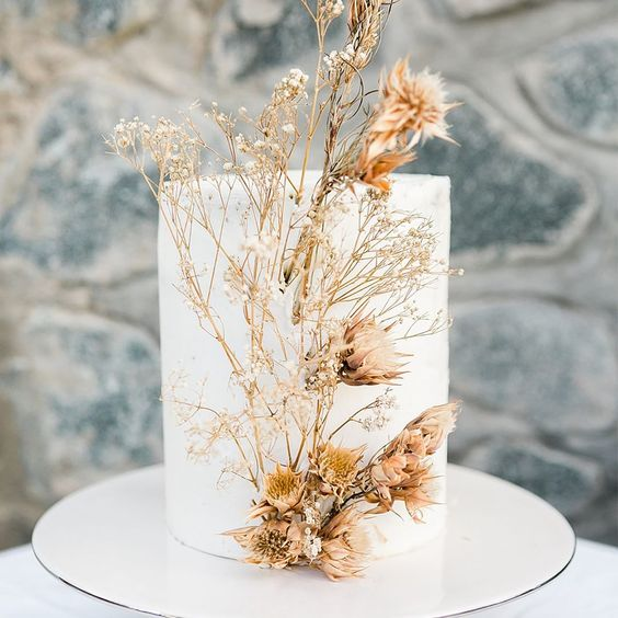 a minimalist white wedding cake decorated with dried blooms looks ethereal and very unusual, idela for the fall