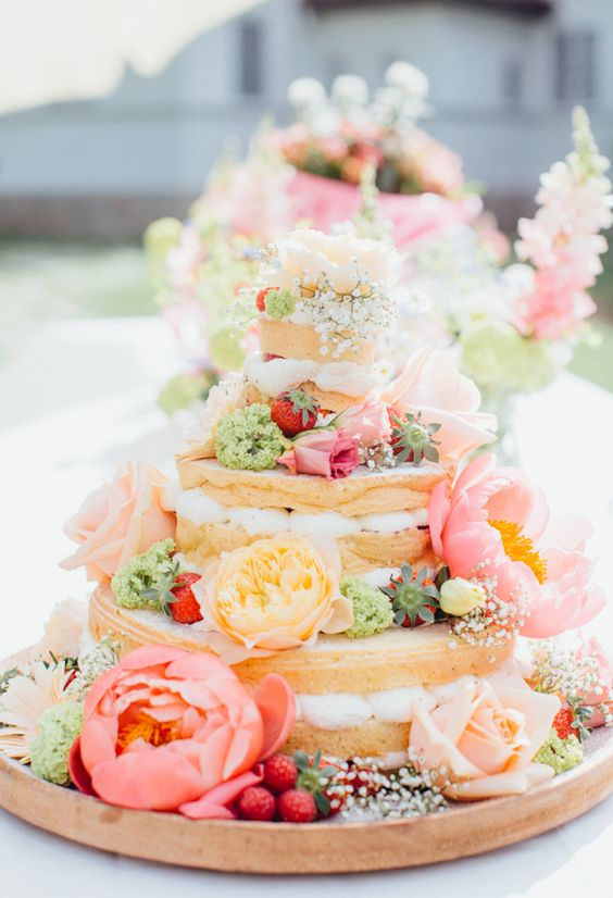 a naked wedding cake decorated with green, sherbet pink and gold blooms and strawberries