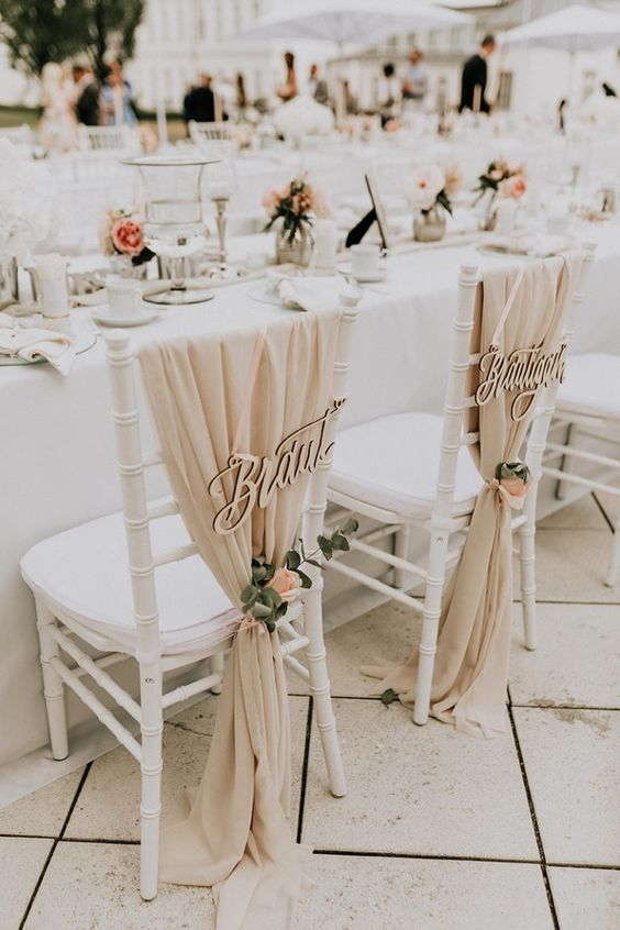 a super chic neutral wedding reception space done with blush blooms and greenery and some photos
