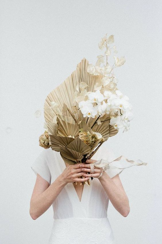 a unique wedding bouquet of gilded leaves, lunaria and white orchids features a very unusual structure