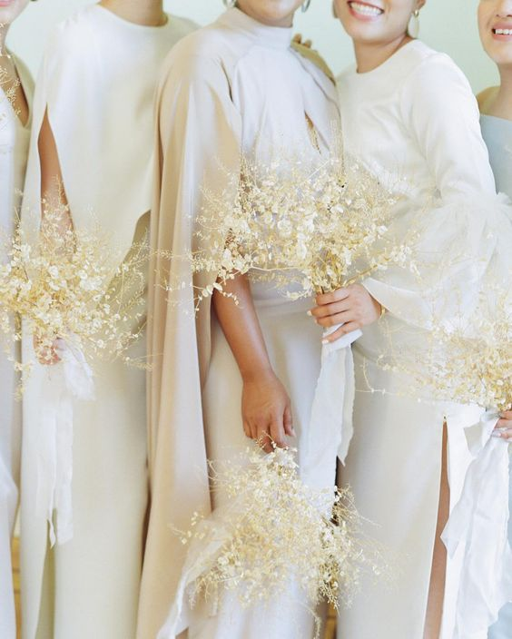 a bride and bridesmaids wearign all-white and carrying white bouquets for a refined look