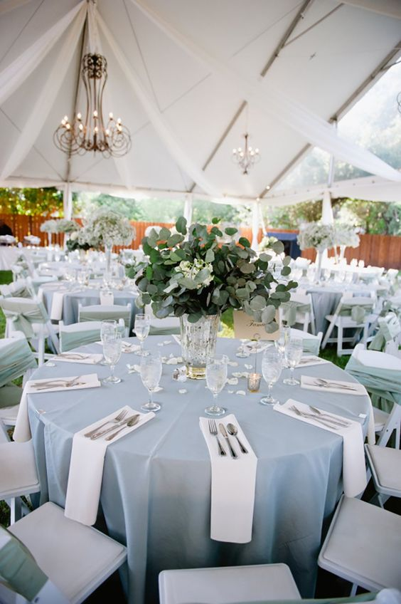 a pastel blue tablecloth and a greenery wedding centerpiece for a tender and refined wedding tablescape