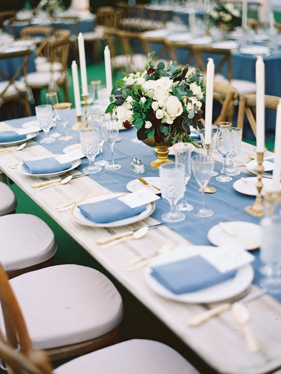 a chic tablescape with a pastel blue table runner, napkins, gold touches and white blooms and greenery