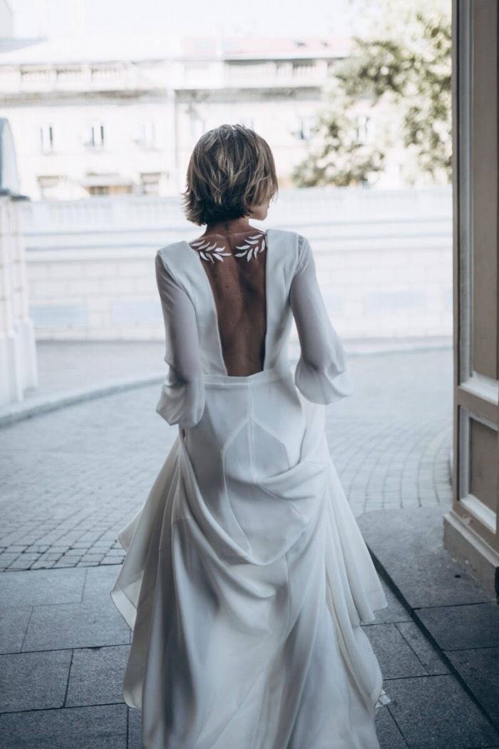 a plain A-line wedding dress with a sheer back with detailing, long sleeves and a train looks cool and catchy
