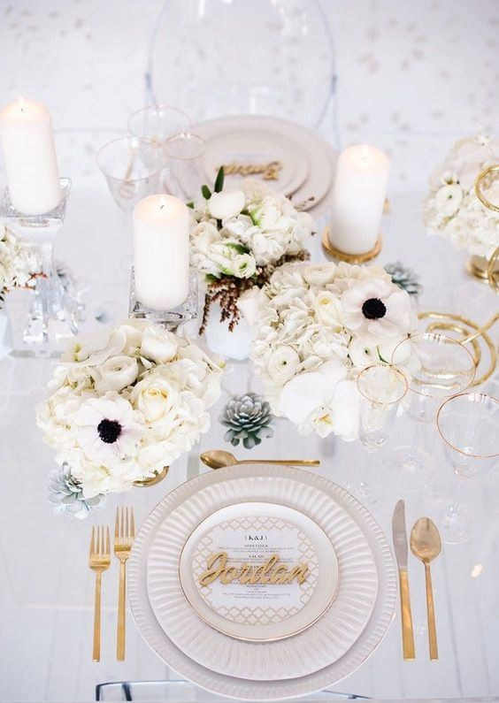 a chic white wedding tablescape with lush blooms, candles and gold touches - cutlery and gold rims